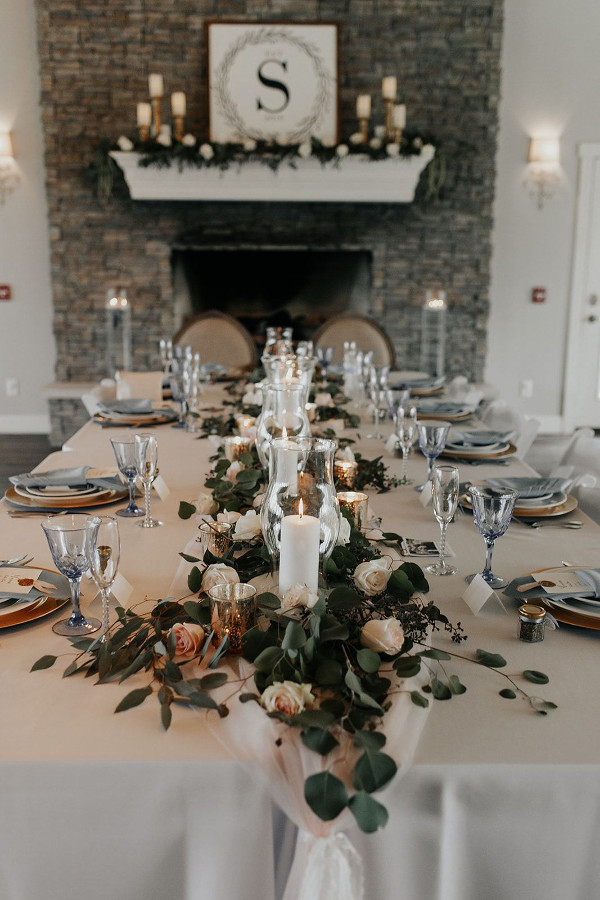 Wedding table with greenery centrepiece, candles and dark linens