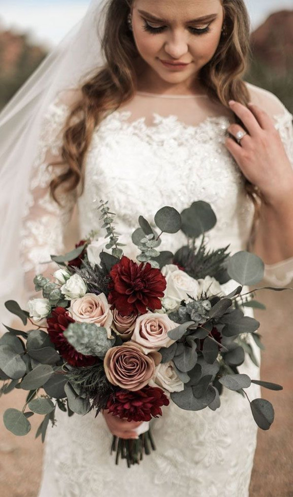 Bride in white lace wedding dress with a bouquet in shades of blush, burgundy, deep red and greenery