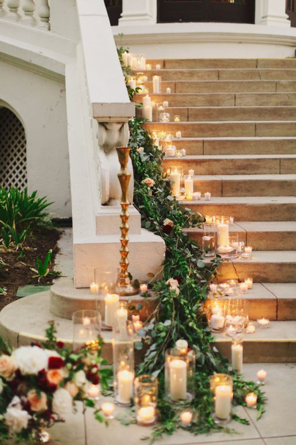Greenery garland sweeting down a candlelit staircase