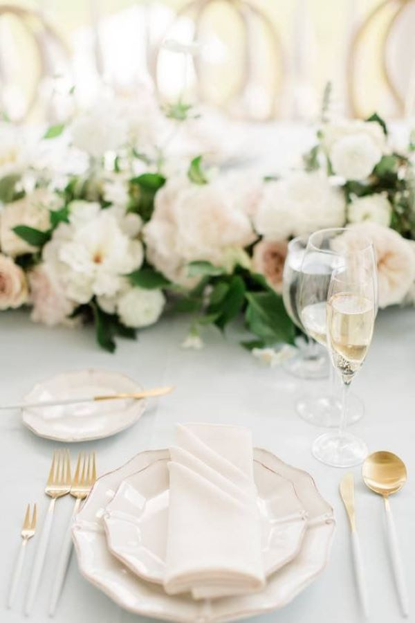 wedding table set up with white handled cutlery and gold rimmed white plates, floral centrepiece with white peonies and greenery