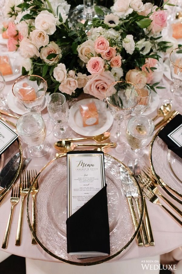 Luxurious tablescape with gold cutlery, glass chargers and dark napkins.  A floral centrepiece of blush, pale pink and burgundy roses
