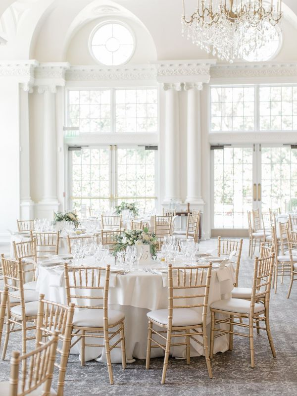 Ballroom with wedding reception tablet up with white linen, chiavari chairs and floral centrepieces
