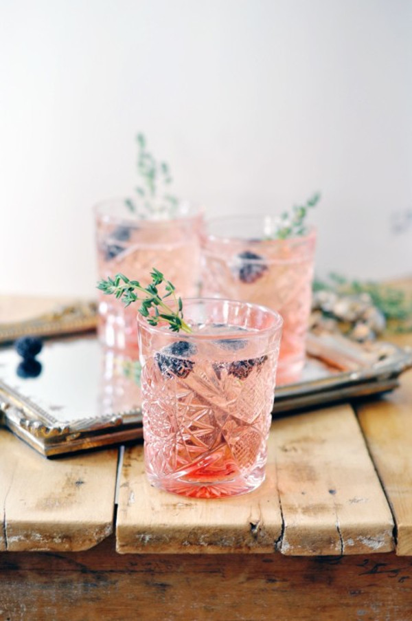 Blackberry and champagne cocktail in crystal glass, with thyme and blackberry garnish