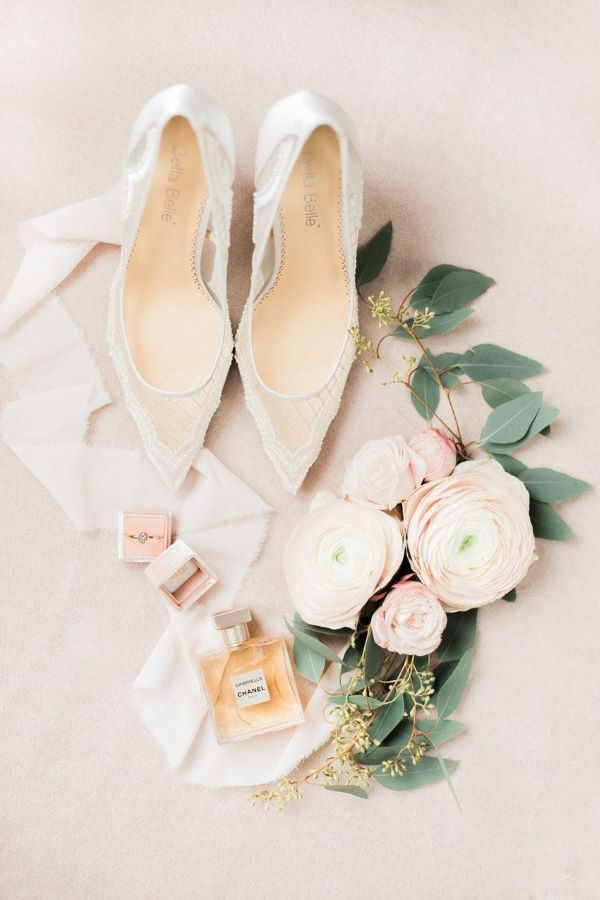 Flat lay with wedding shoes, peonies, Chanel perfume and wedding rings