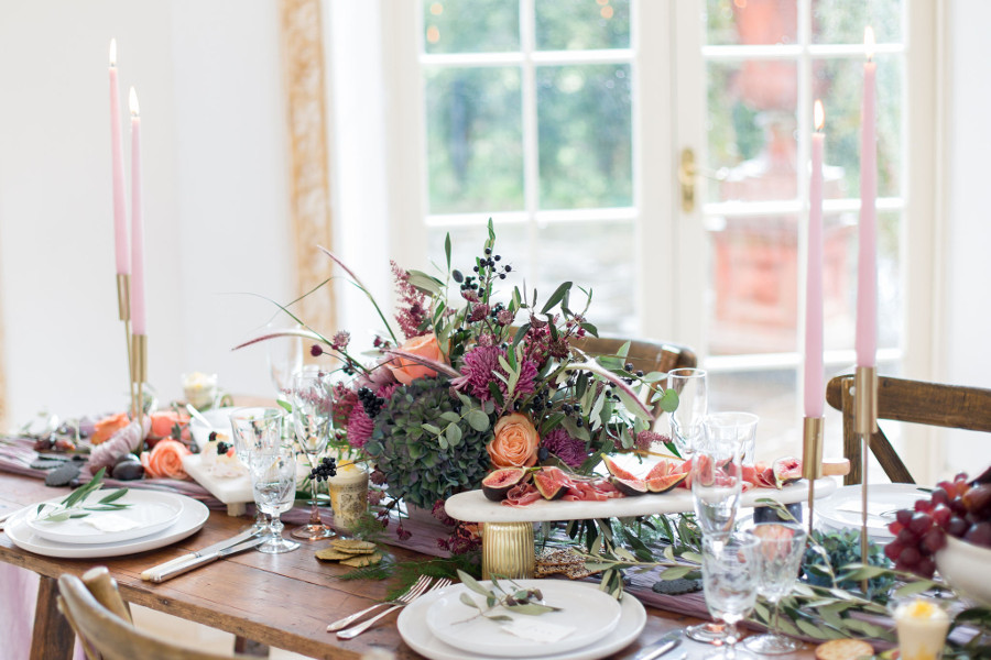 Table set with glassware, candles and grazing platters