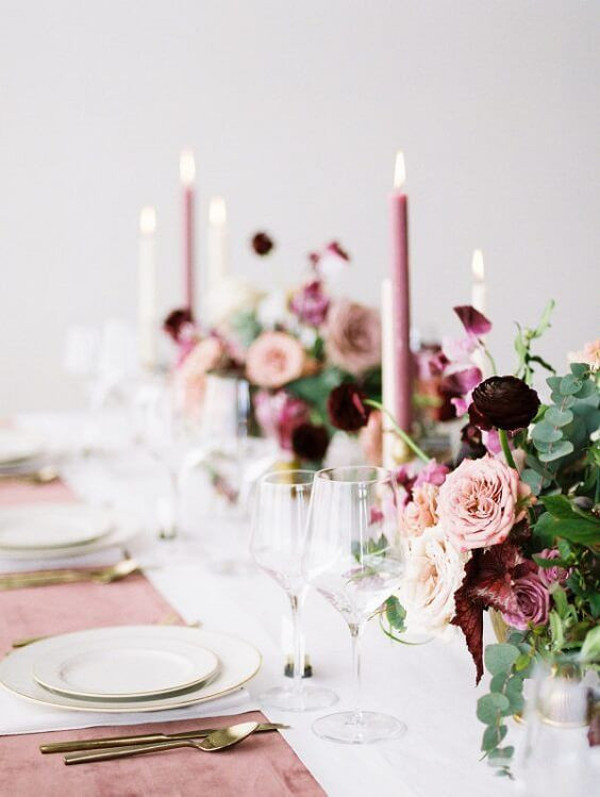 Wedding table set with plates, cutlery and blush and burgundy flowers
