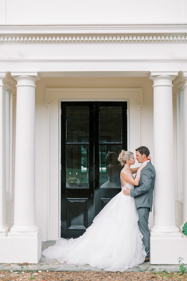 Bride & groom posing outside door to garden of Morden Hall, historic wedding venue in London.  Georgina Alexander Weddings Luxury Surrey Wedding Planner UK