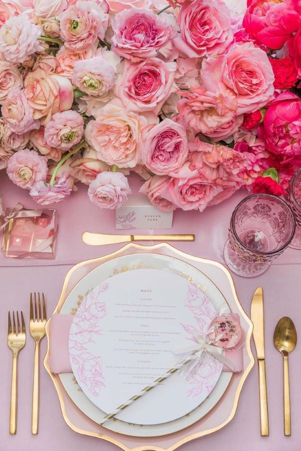 pink and gold wedding table setting with roses and gold cutlery