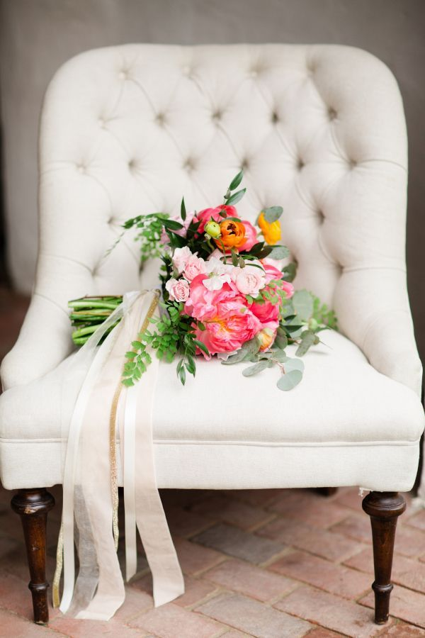 wedding bouquet with peonies and roses with pink ribbon on white chair