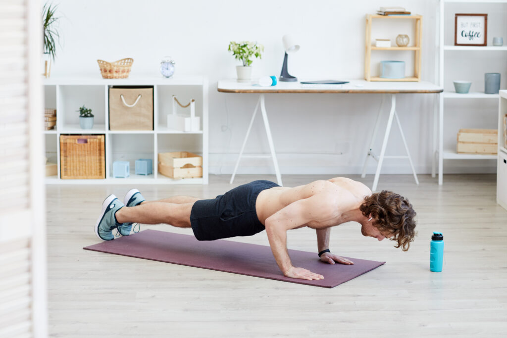 Healthy shirtless man doing push-ups on exercise mat during sports training at home