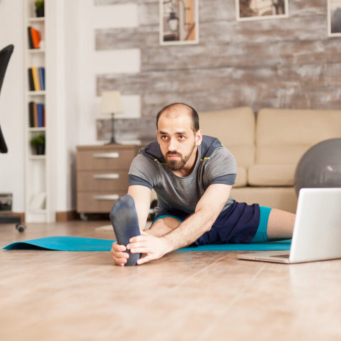 Man doing legs stretching on yoga mat from online training during global lockdown.