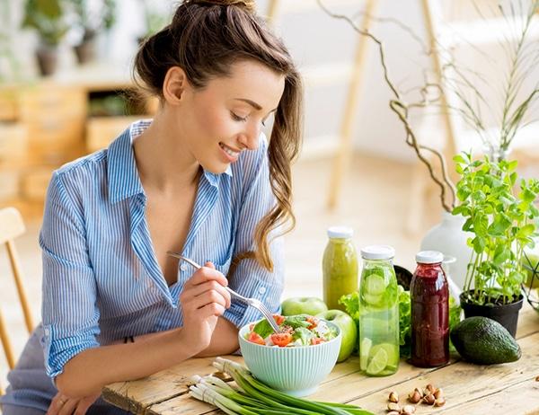 happy-healthy-woman-eating-folic-acid-rich-salad