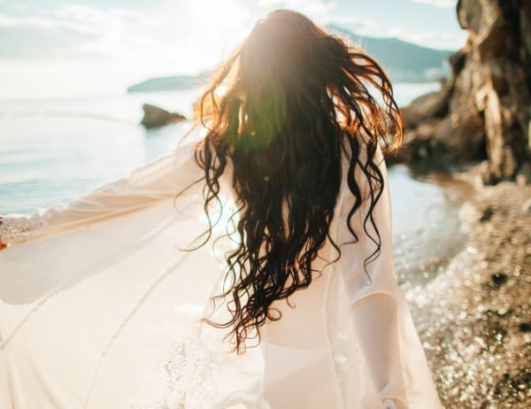 Healthy Woman Running dreamy with wind in hair and sunflare on beach sunset