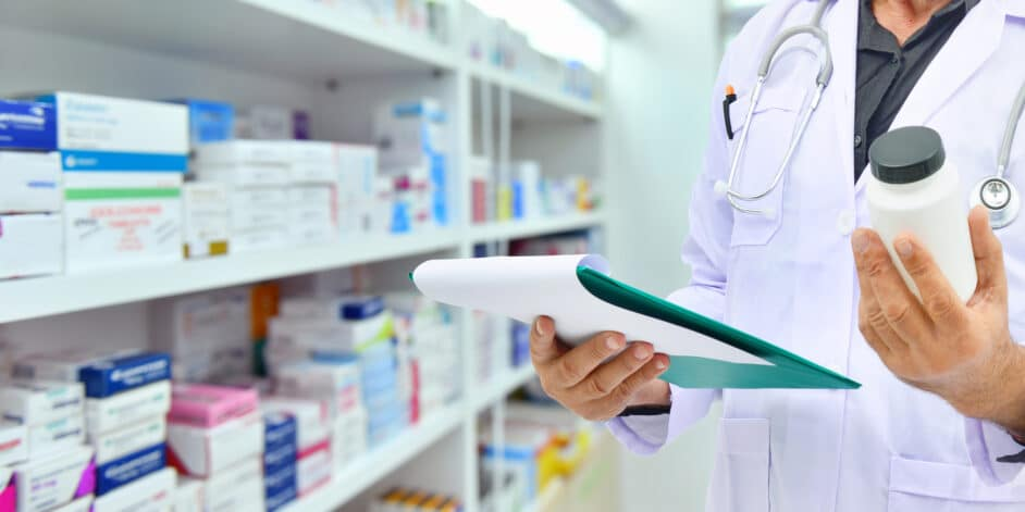 Pharmacist_holding_medicine bottle and computer tablet for filling prescription_in_pharmacy_drugstore