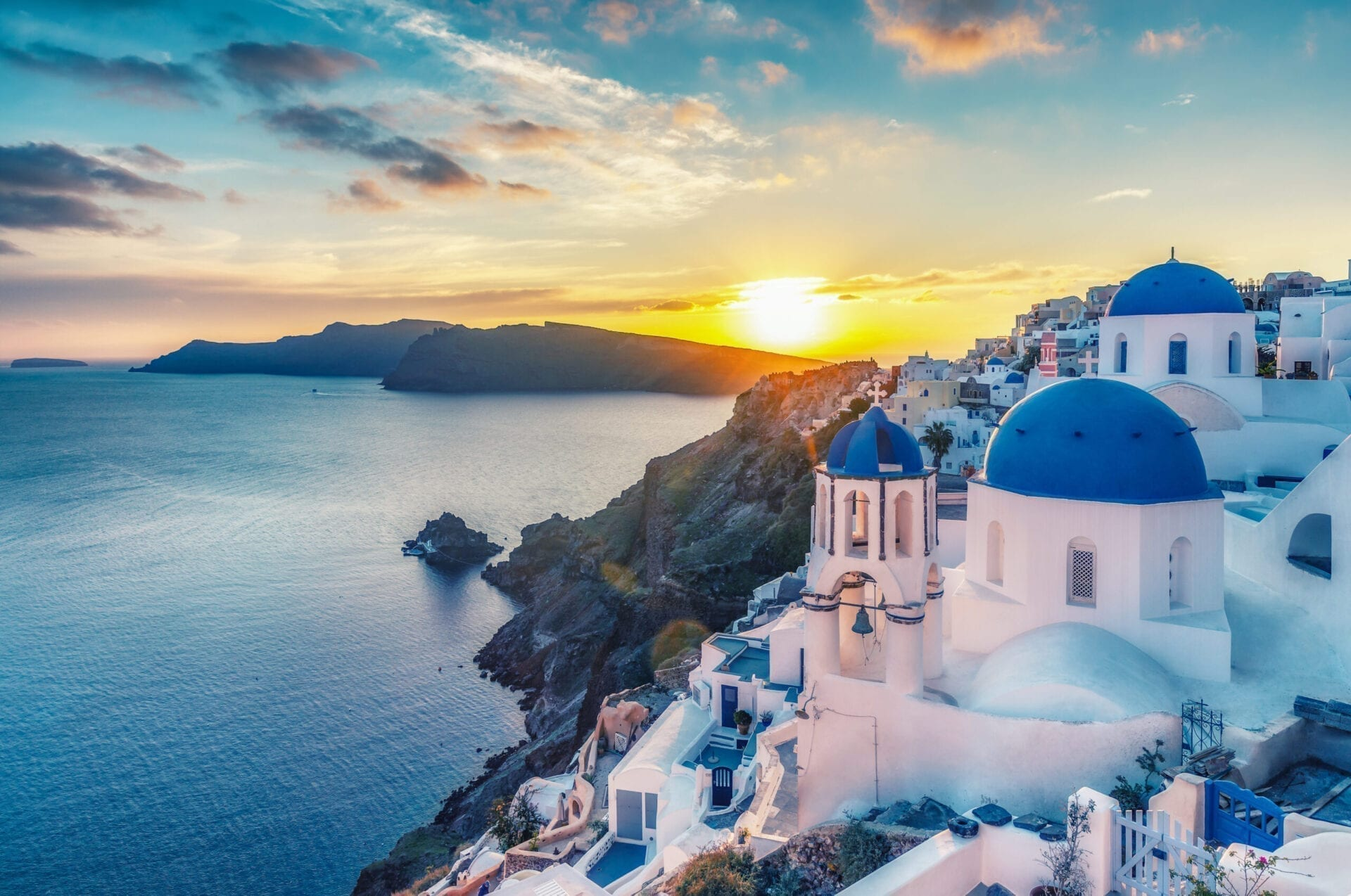 Beautiful view of Churches in Oia village, Santorini island in Greece at sunset, with dramatic sky.