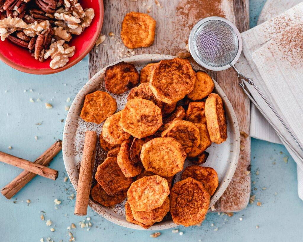 Baked sweet potato on a chopping board, sprinkled with cinnamon