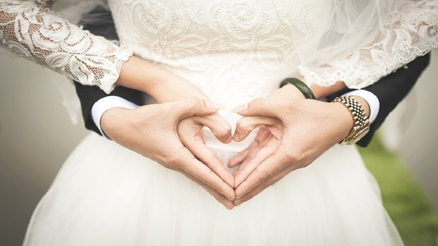 Two healthcare workers hold socially distant wedding