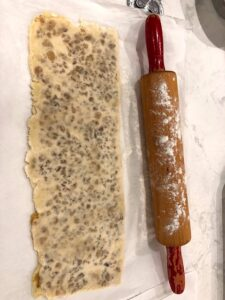 The dough is folded over onto itself. A rolling pin is used to press the raisins into the dough | urbnspice.com
