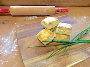 Asiago Scones are stacked on a board