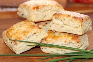 Asiago Cheese and Chive Scones on a breadboard | urbnspice.com