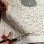 Cutting out circular DIY reusable beeswax wrap from fabric.