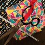 Scissors, tape and fabric for DIY reusable beeswax wraps.