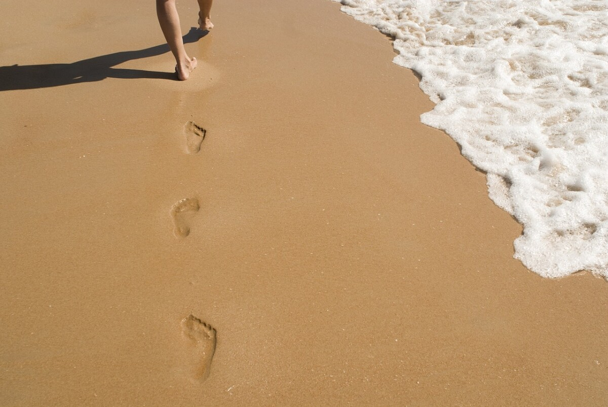 woman-walking-footprints-in-the-sand