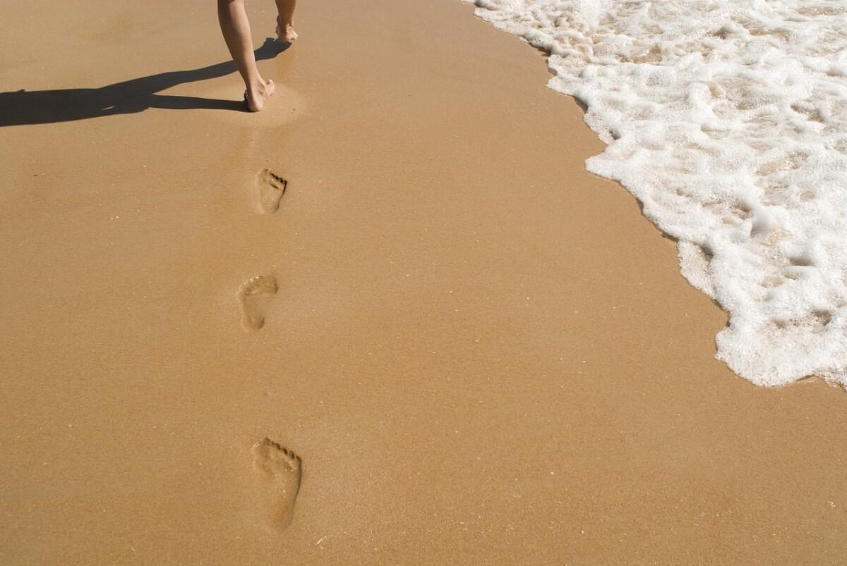 woman-walking-footprints-in-the-sand