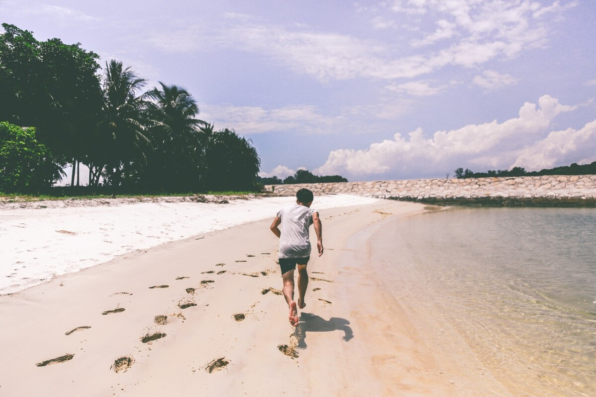man-running-on-beach-with-palm-trees
