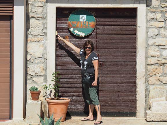 Woman-Ringing-Doorbell-For-Wine-Korcula-Island-Croatia