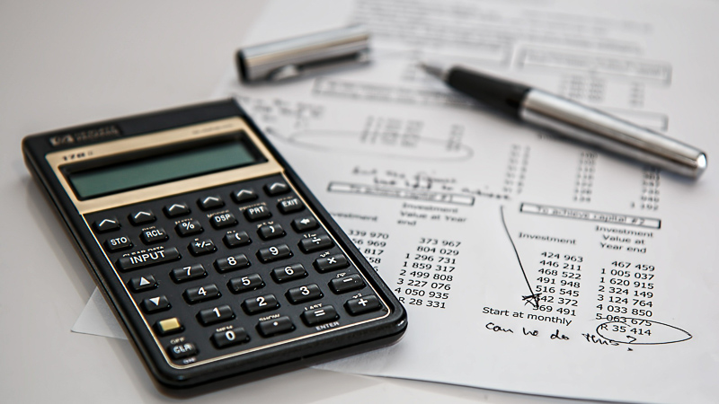 Calculator and pen near financial document
