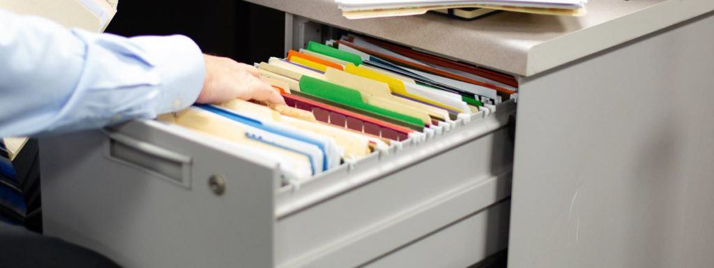 Business professional searching through file folder drawer
