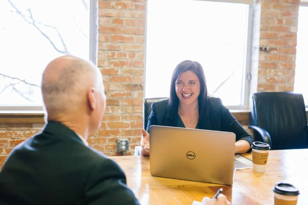 lady smiling at a man across from her at a table with a dell laptop