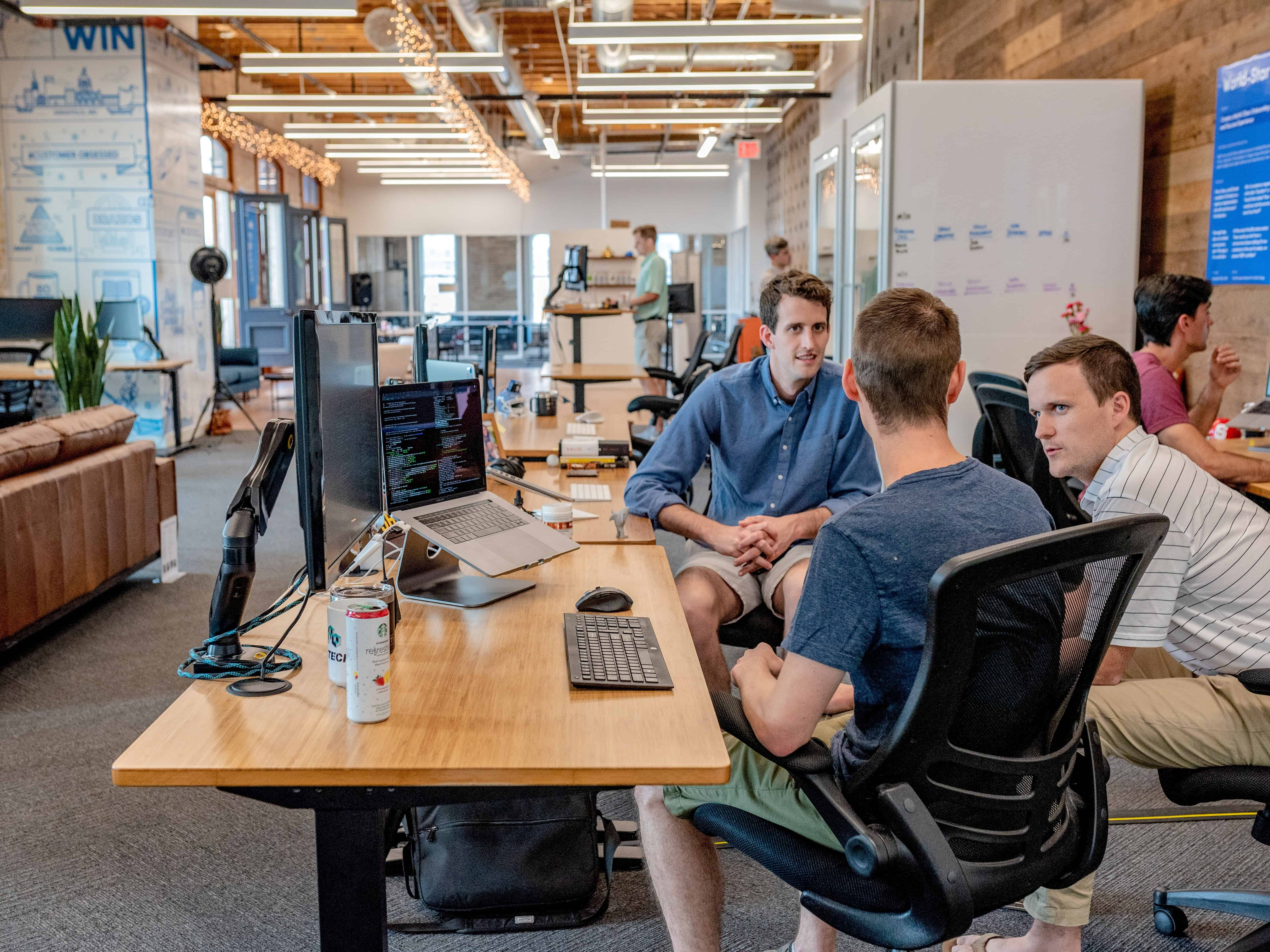 three people meeting at a desk in a open concept startup office