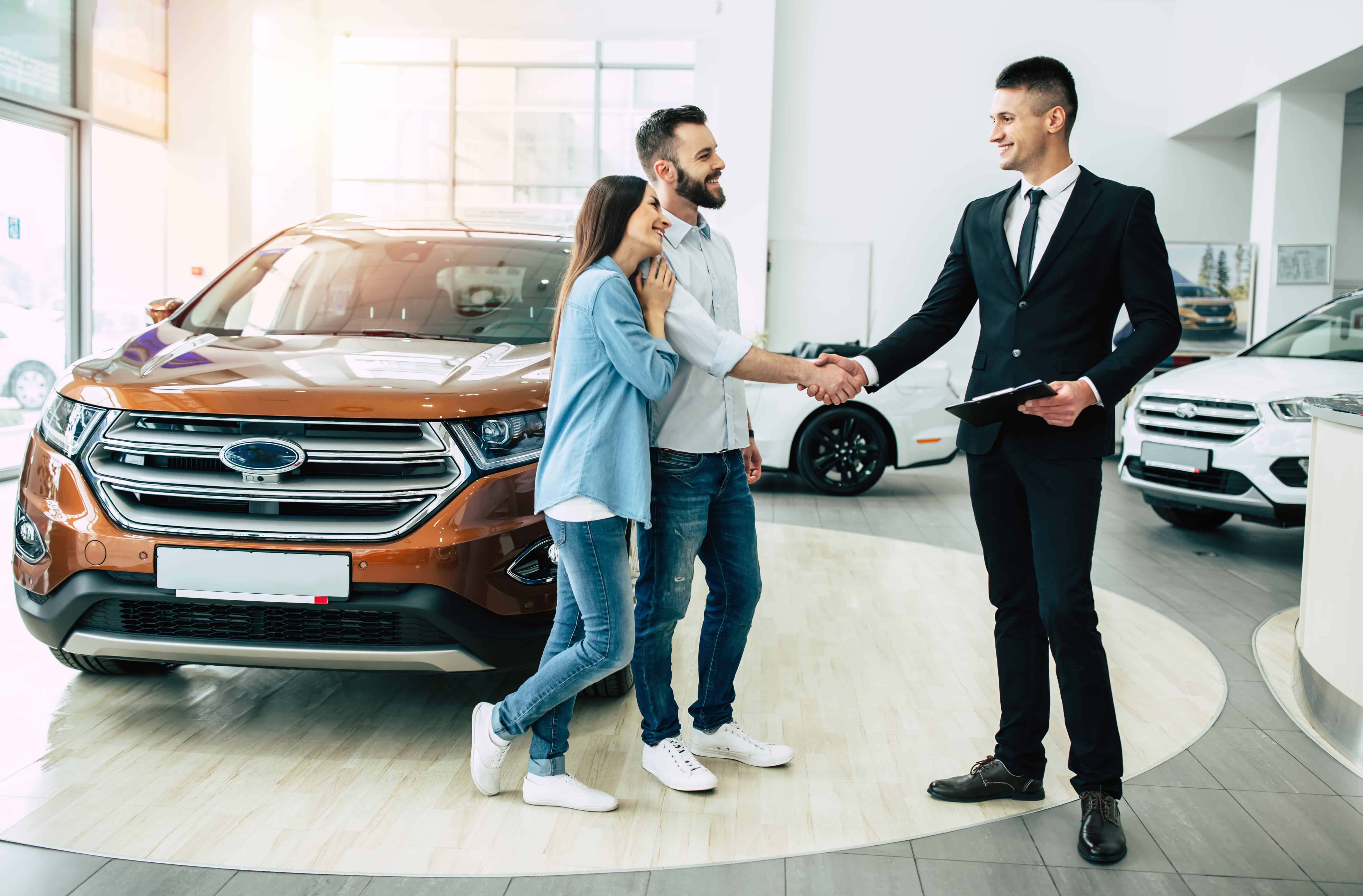 Car salesman shaking hands with a couple in the showroom in front of a suv