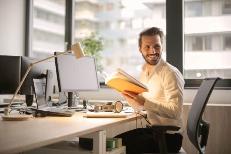 Man using a docking station at his desk smiling