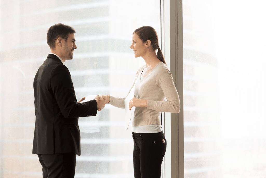 Female HR director shaking hands with new male employee