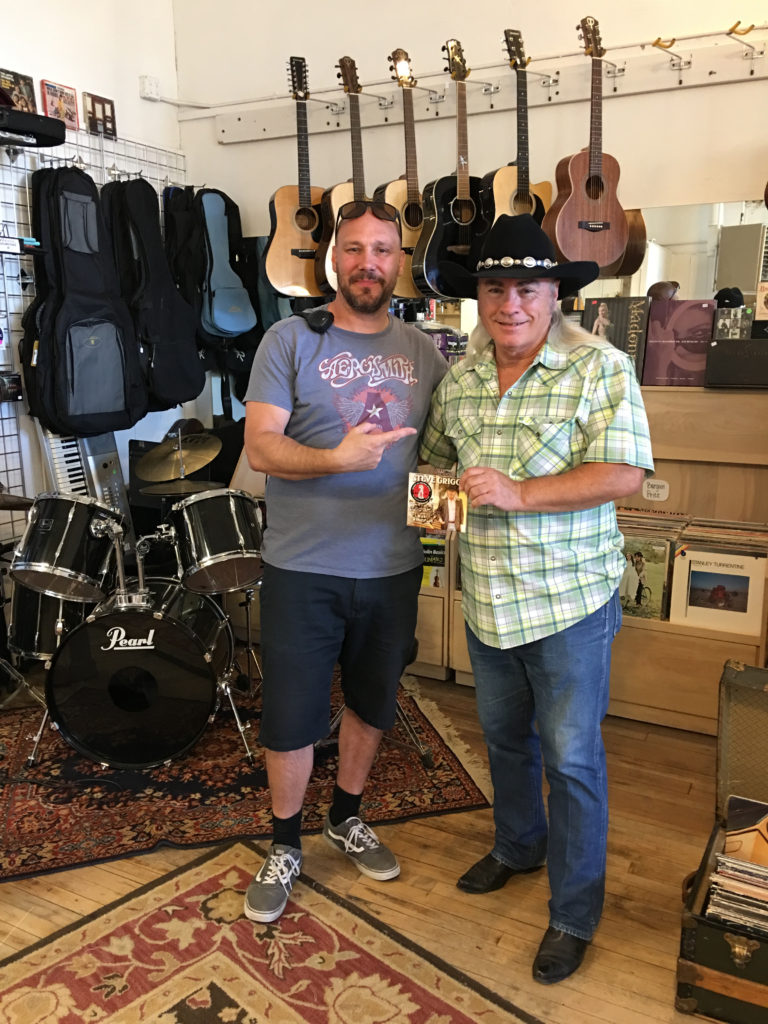 Steve Griggs poses with fan in a music store.