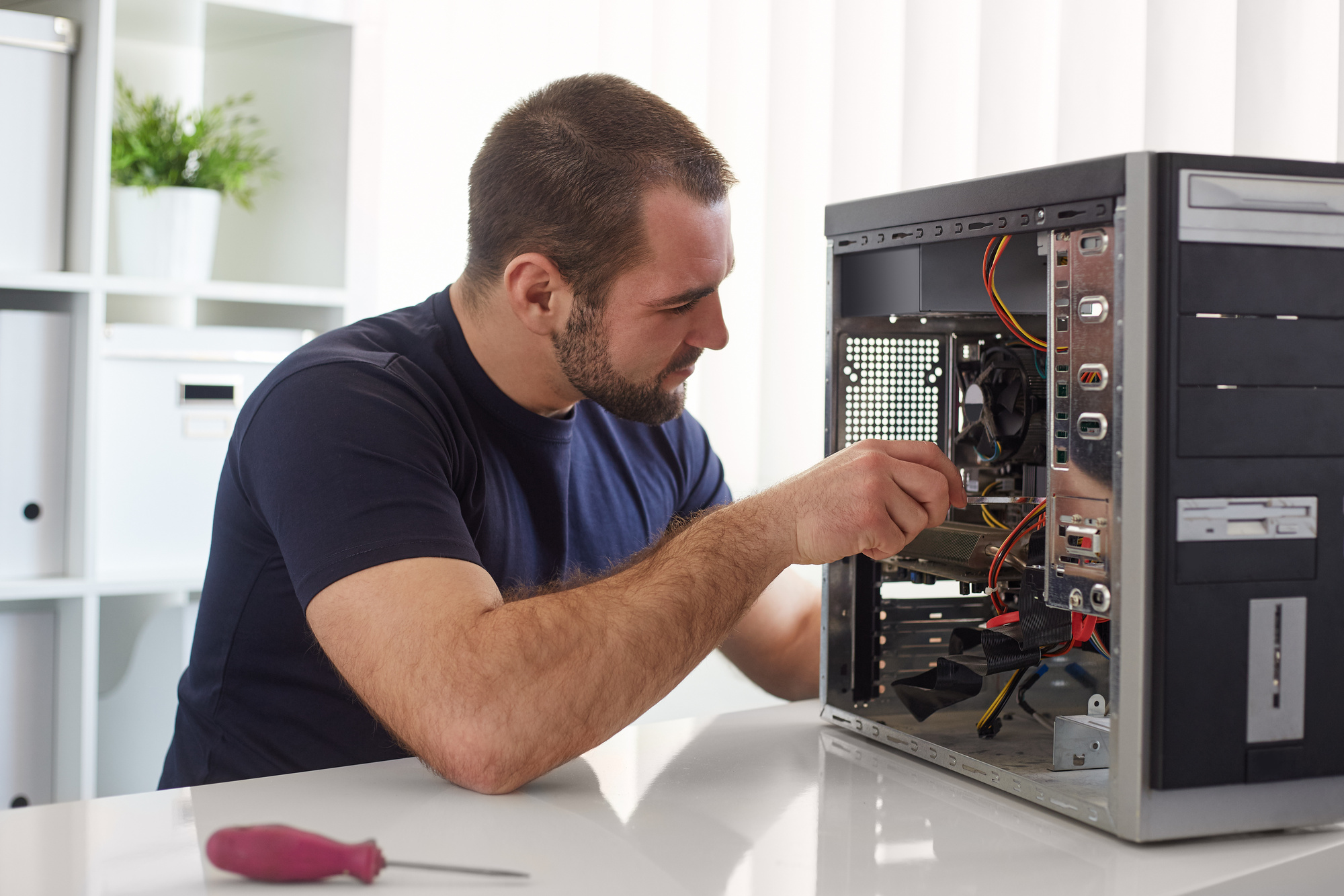 Young man repairing computer while sitting at his working place