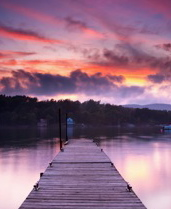 Contact - Photo of a dock, lake and fiery sunset