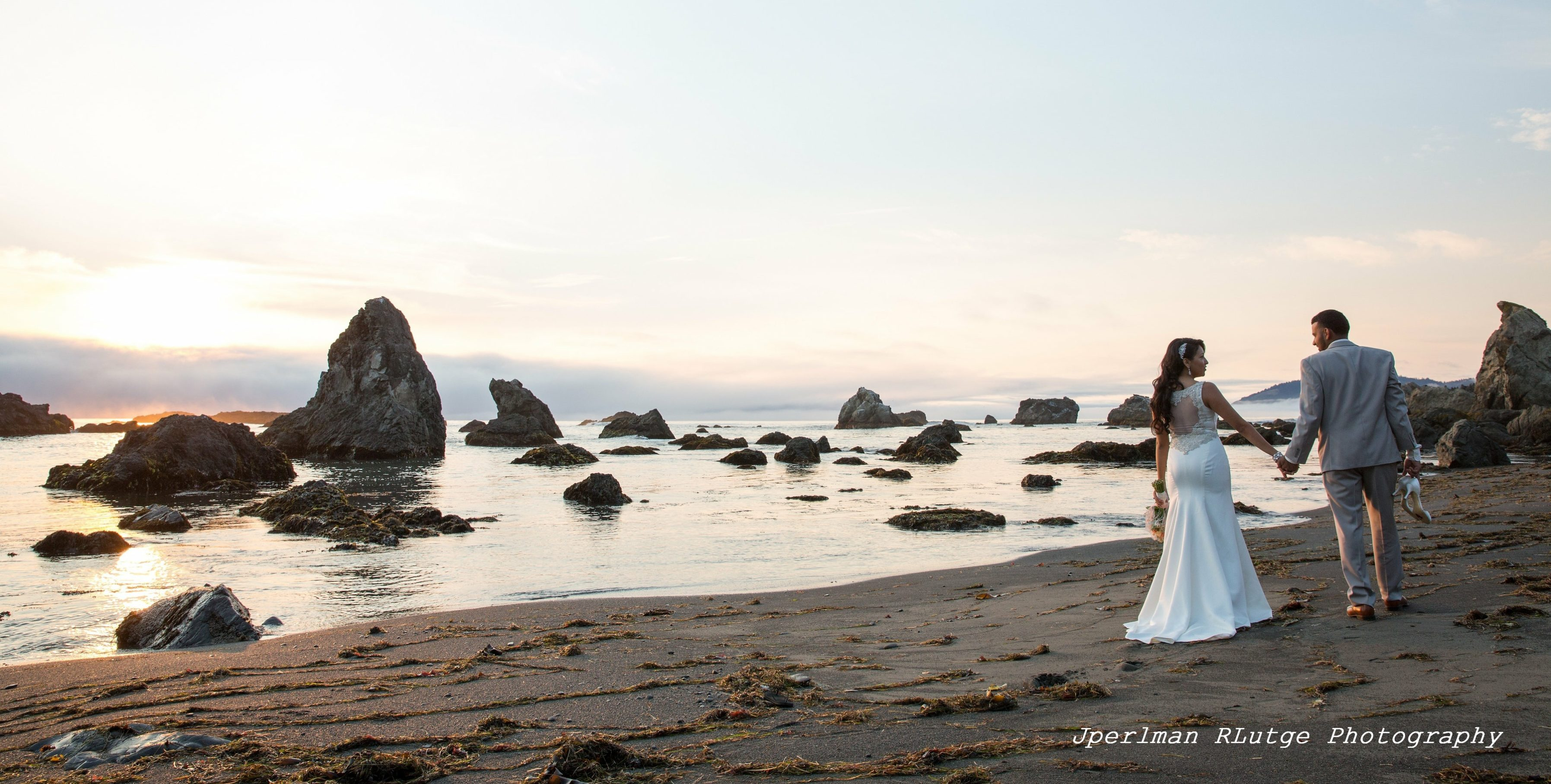 Johana and Isaac, after their Elope Mendocino wedding, stroll on the beach at Westport as the sun sets.