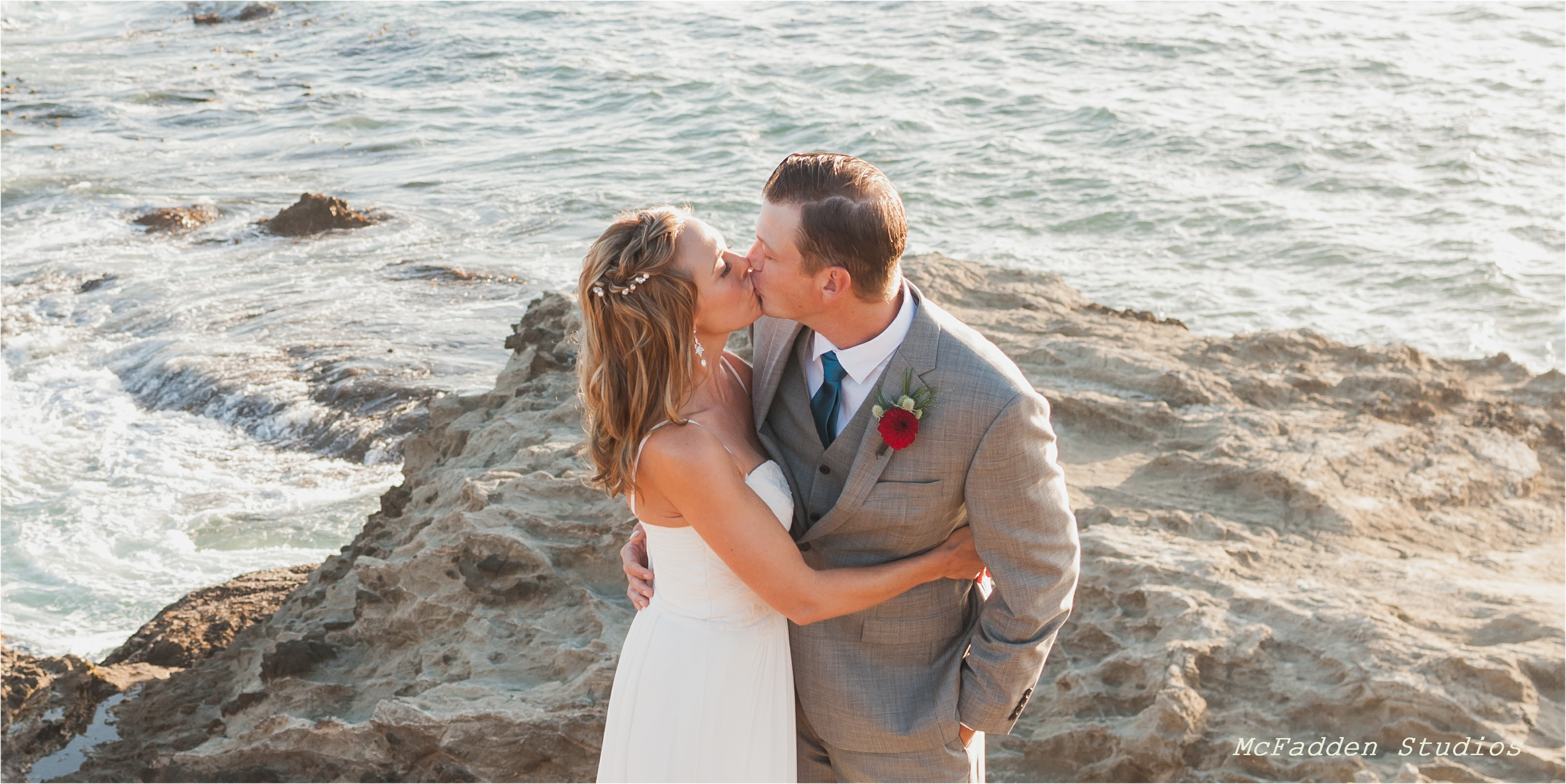 Not long after their Elope Mendocino wedding, Megan and Shane exchange a kiss as the ocean crashes on the rocks offshore.