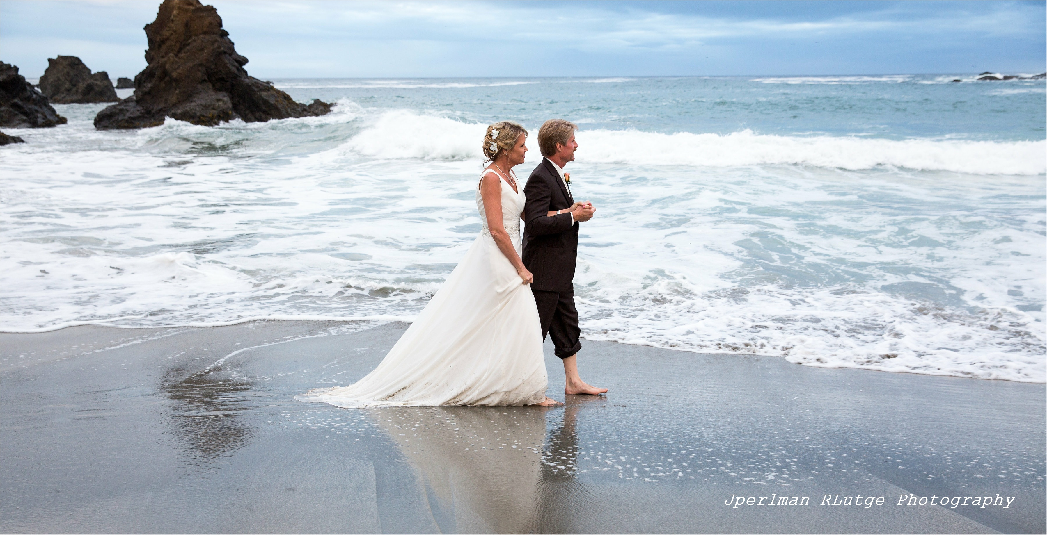 The surf laps their bare feet as Kim and David stroll Jug Handle Beach after their Elope Mendocino ceremony.