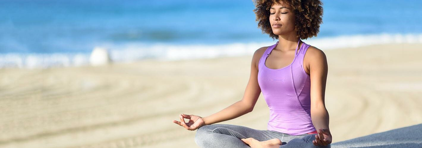A woman meditating on the beach in athletic gear