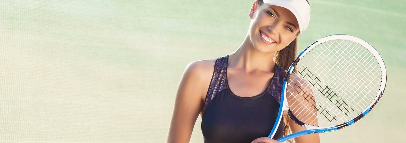 A woman in athletic gear holding a tennis racket and smiling