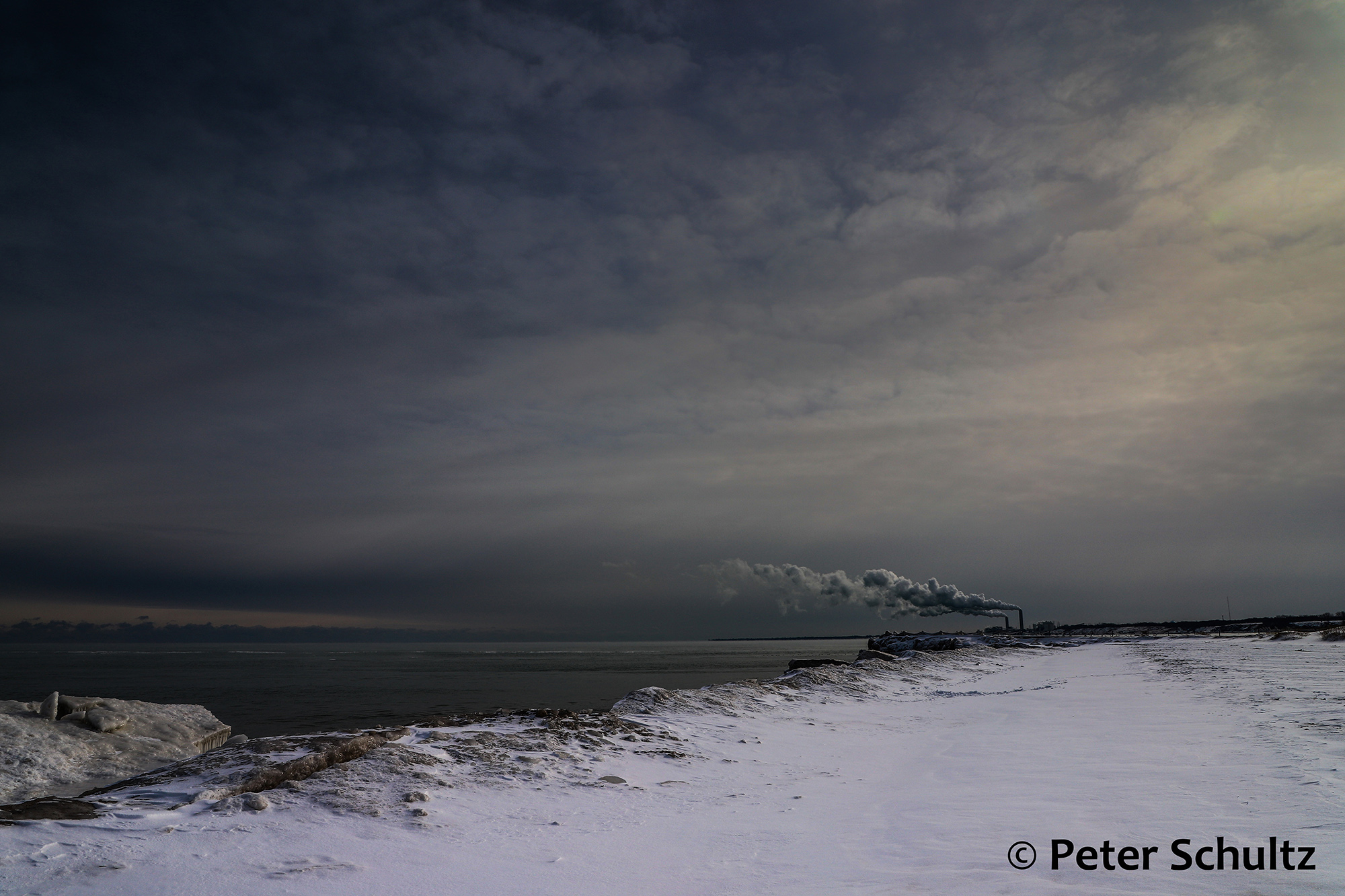 A power plant pumps smoke into the sky on the frozen shoreline of Lake Michigan