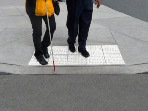 A person is being helped across the street that has a cane. The raised sidewalk and legs of the people walking are shown.