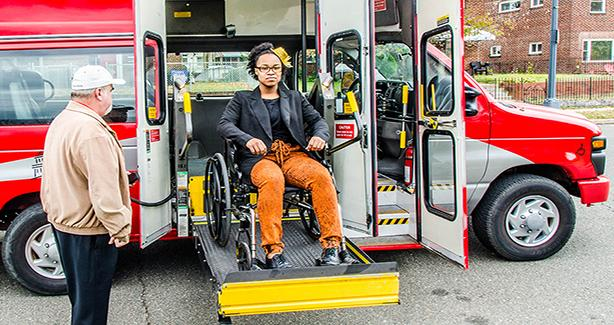 Photo of woman in a wheelchair exiting accessible van on a chair lift