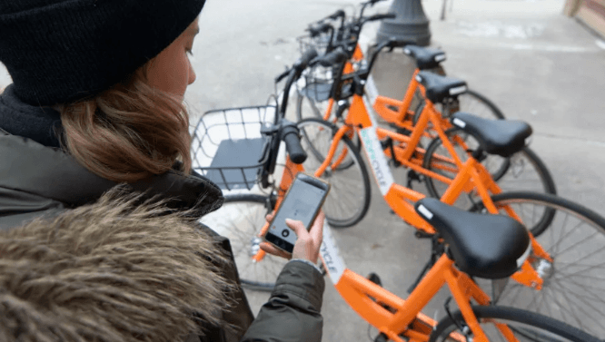 Woman checking out Koloni bike on smartphone