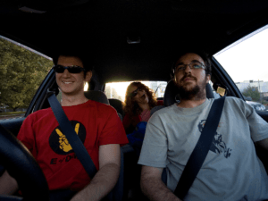 Photo of three people smiling and riding in a car